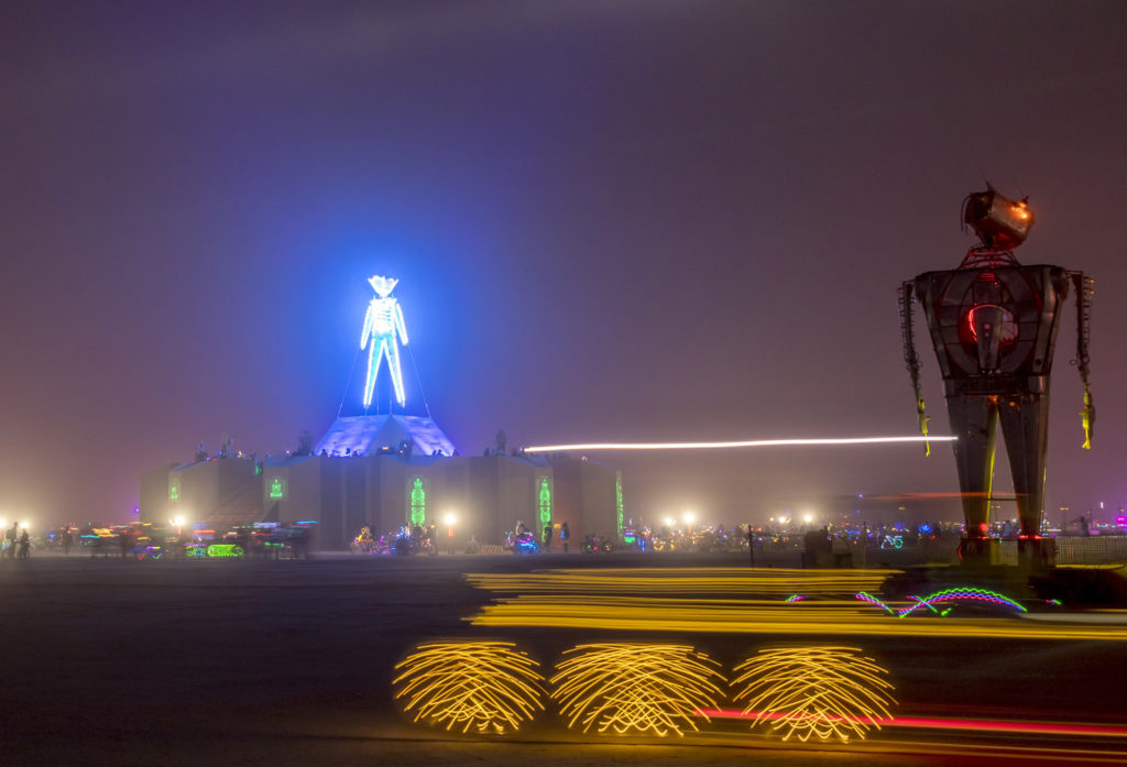 The Man at Burning Man with a robot and light trails in the foreground