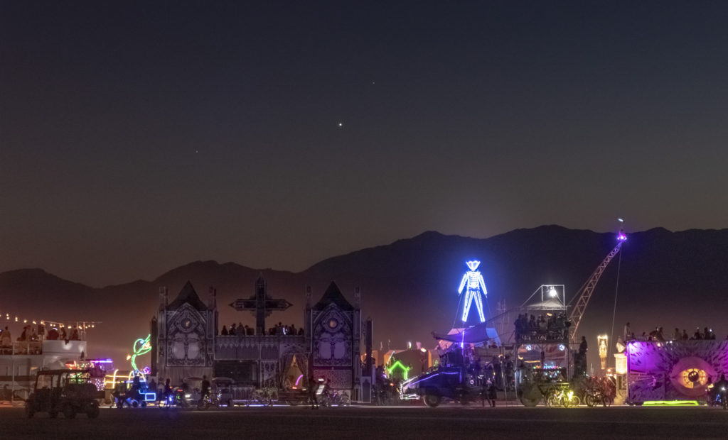 The Man at Burning Man with a bunch of art cars including a cathedral