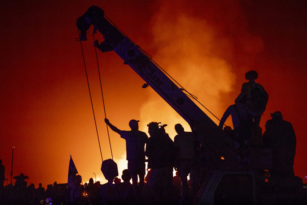 People lounging on crane in front of Temple Burn at Burning Man
