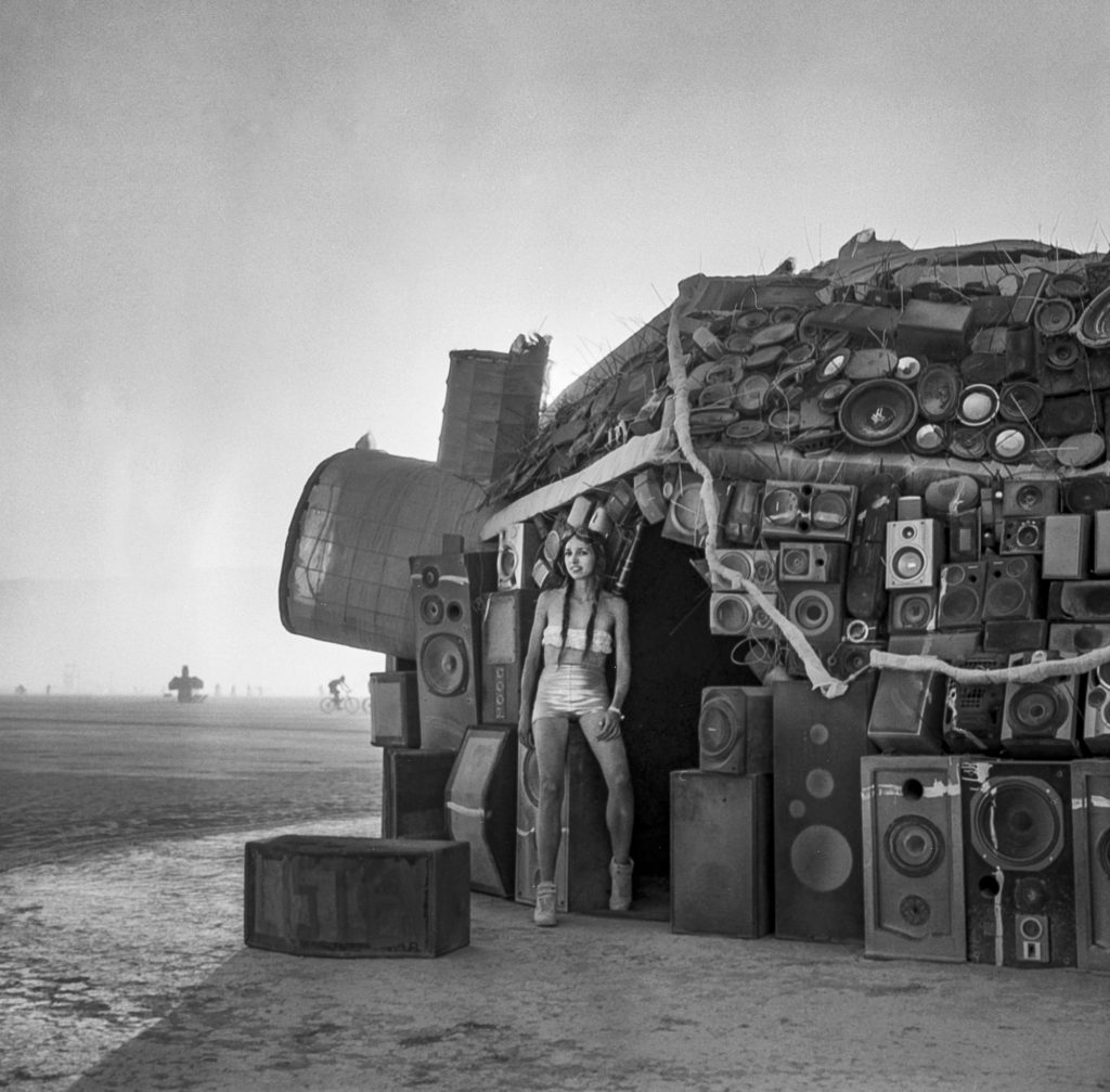 Building made of speakers with artist posing at Burning Man